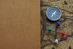 Compass and notebook on blur vintage world map, journey concept, copy space. Compass, pins and notebook on blur vintage world map, journey concept, copy space Stock Images