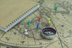 Compass and notebook on blur vintage world map, journey concept, copy space. Compass, pins and notebook on blur vintage world map, journey concept, copy space Royalty Free Stock Photography
