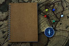 Compass and notebook on blur vintage world map, journey concept, copy space. Compass` pins and notebook on blur vintage world map, journey concept, copy space Stock Image