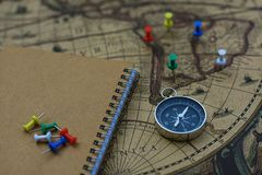 Compass and notebook on blur vintage world map, journey concept, copy space. Compass, pins and notebook on blur vintage world map, journey concept, copy space Stock Photos