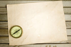 Compass and old paper. On wood background Royalty Free Stock Photo
