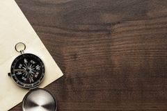 Compass and old paper on the brown wooden table. Background Royalty Free Stock Image