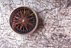 Compass on old paper. Vintage compass lying on old map with copy space Stock Photos