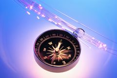 Compass and Optical Fibres. On Blue Background royalty free stock photos