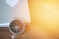 Compass over the book on wooden table with light flare and copy space Stock Photos