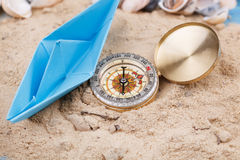 Compass and paper boat in the sand Stock Photography