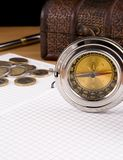 Compass, pen and coin on notebook Royalty Free Stock Photo