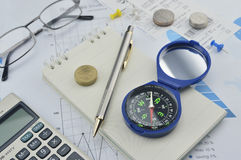 Compass, pen and coin on notebook, accounting background Royalty Free Stock Image