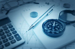 Compass, pen and coin on notebook, accounting background Royalty Free Stock Photography