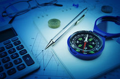Compass, pen, glasses and coin on notebook, business vision concept Stock Image