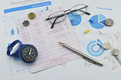 Compass, pen, glasses and coin on saving book, accounting background Stock Photos