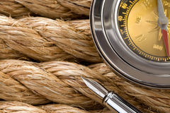 Compass with pen on ship ropes. Compass with ink pen on ship ropes Stock Photo