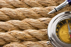 Compass with pen on ship ropes Royalty Free Stock Image