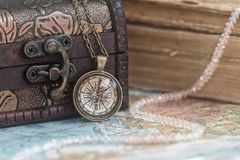 Compass pendant and casket with old books royalty free stock photography