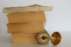 Compass on pile of old books. royalty free stock images