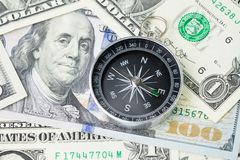Compass and pile of US dollar money banknote, investment, financial crisis or economic direction concept.  stock photography