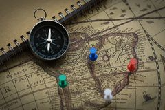 Compass and notebook on blur vintage world map, journey concept, copy space. Compass, pins and notebook on blur vintage world map, journey concept, copy space Royalty Free Stock Photo