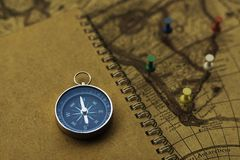 Compass and notebook on blur vintage world map, journey concept, copy space. Compass, pins and notebook on blur vintage world map, journey concept, copy space Royalty Free Stock Image