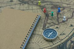Compass and notebook on blur vintage world map, journey concept, copy space. Compass, pins and notebook on blur vintage world map, journey concept, copy space Stock Photography
