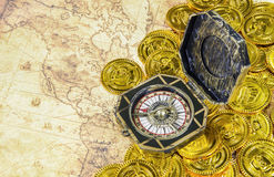 Compass and pirate golden coin on a old world map Royalty Free Stock Images