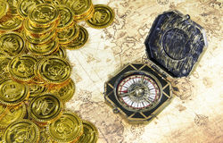 Compass and pirate golden coin on a old world map Royalty Free Stock Photos
