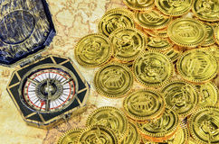 Compass and pirate golden coin on a old world map Royalty Free Stock Image