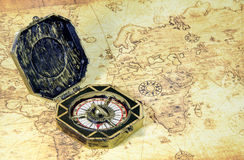 Compass and pirate golden coin on a old world map Royalty Free Stock Photography