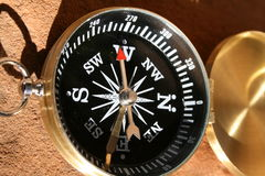 Compass Points West. A brass compass on a rock pointing stock image
