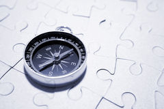 Compass On Puzzle. Black and silver compass on attached white puzzle pieces.  Conceptual Stock Photo