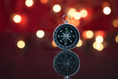 Compass with red background and bokeh of decoration light on par royalty free stock images