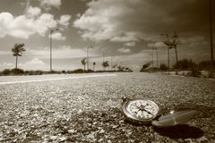 Compass on the road. Compass open on a highway. Photo format black and white square. Snails on the asphalt. Clouds on the horizon stock images