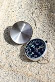 Compass on rock. An antique compass pointing north on a granite rock background Royalty Free Stock Image
