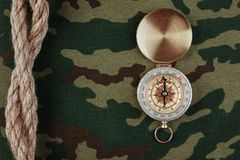 Compass and rope on a camouflage. Background stock photography