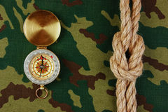 Compass and rope on a camouflage. Background stock images