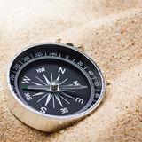 Compass in the sand lit by the rays Stock Images
