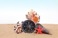 Compass, seashells on and starfish the sea sand Stock Photography