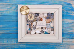 compass, shell and sign life is adventure Royalty Free Stock Photo