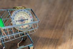 Compass in shopping cart. Vintage compass in shopping cart on wood. table Royalty Free Stock Image