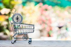 Compass in shopping cart. Vintage compass in shopping cart on wood table stock photos