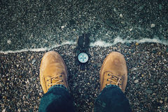 Compass on shore. Compass on pebble shore near legs of traveler man outdoor. Point of view shot Stock Images