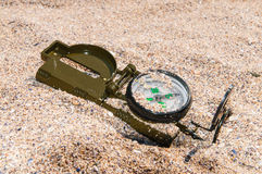 Compass showing a directions on sea sand. Compass showing a direction, lies on sea sand Royalty Free Stock Photos