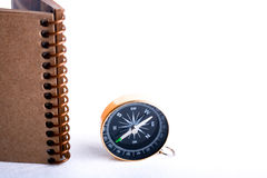 Compass and spiral notebook. Compass by the side of a  spiral notebook on a white background Stock Photos