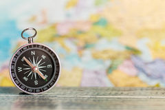 Compass on the table against the background of a tourist map Royalty Free Stock Images