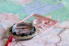 Compass and a topographic map. Compass on top of a topographic map Stock Images