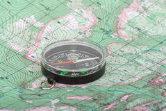 Compass on topographical map. Close up of compass on topographical map Royalty Free Stock Photography