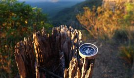 Compass on tree stump. An antique compass pointing north resting on a tree stump at sunset Stock Image