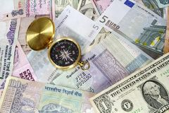 Compass on Various Currencies. Compass on various international currency bills Royalty Free Stock Photos