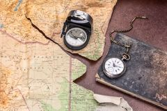 Compass vintage map torn with pocket watch on ancient diary Royalty Free Stock Image