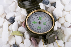 Compass on white pebbles. Closeup of compass on white and colored smooth pebbles Stock Image