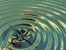 The compass (wind rose) in the water. The waves, the reflections of the sky, sun, clouds Royalty Free Stock Photography